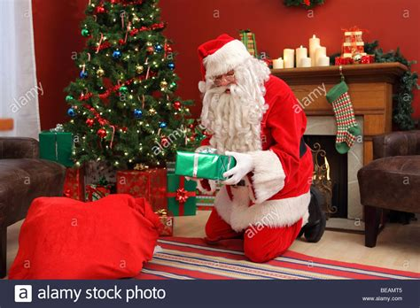 Santa Claus Putting Gifts Under Christmas Tree Stock Photo