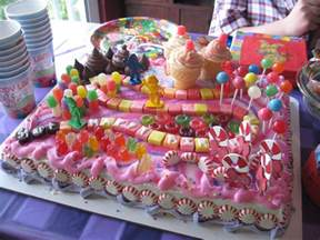 wide pink cake using colorful decoration ideas with snake and ladder details and lollipops