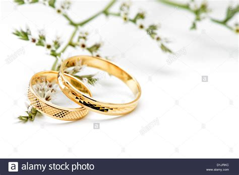gold wedding rings and branch flowers isolated on white