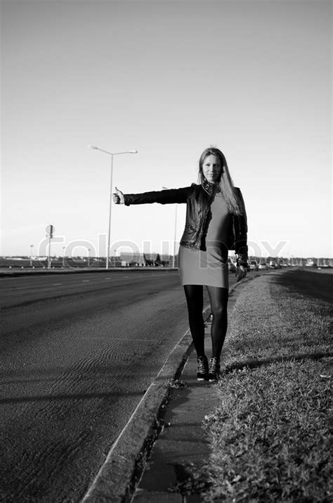 Girl on the road waiting for a car, black and white photo