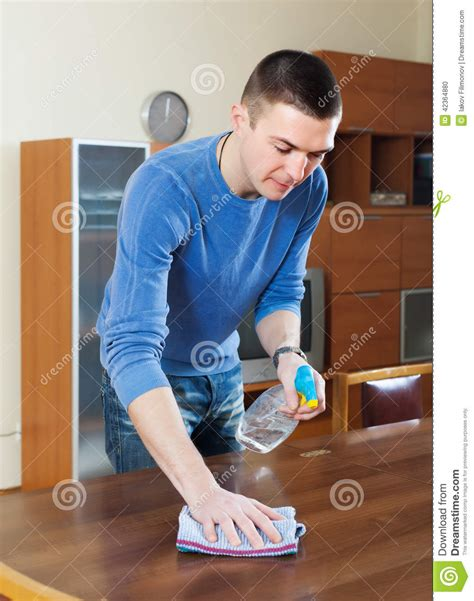 cleaning houses under the table man cleaning table with rag and cleanser stock photo