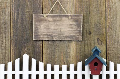 blank wood sign hanging  white picket fence