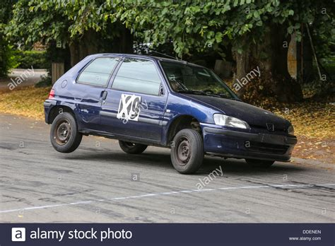 old peugeot old peugeot 106 rally car taking a curve on 3 wheels stock