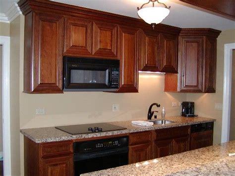 cherry cabinets black appliances  warm tones