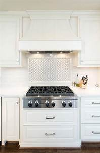 A white paneled french kitchen hood stands over a white for Kitchen backsplash over stove