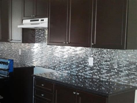 gray small tile back splash with dark brown wooden cabinet