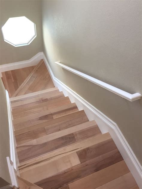 natural maple wood stairs white baseboards beach house