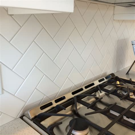 3x6 white subway tile in a herringbone pattern with light gray grout finishes floors walls
