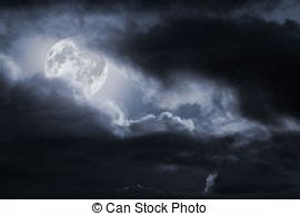 moon in eerie white clouds against a black sky