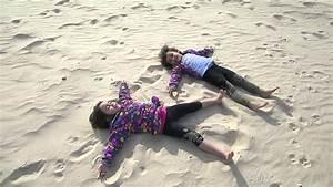 The girls making sand angels on the beach - YouTube