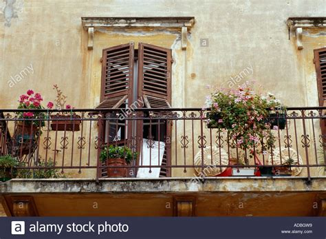 Elegant Ironwork Balcony With Flowerpots And Old Wooden