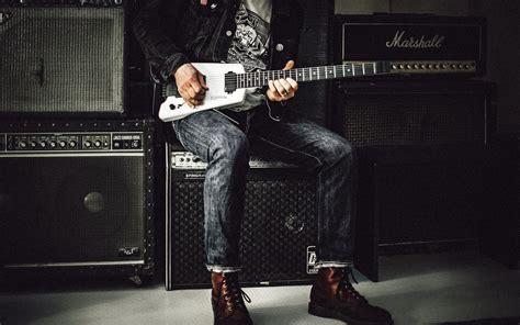 man sitting  guitar amplifier playing electric guitar