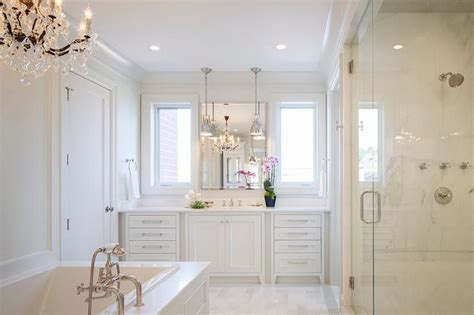 all white master bathroom with chandelier over tub