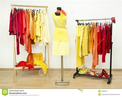 wardrobe with yellow orange and clothes arranged on