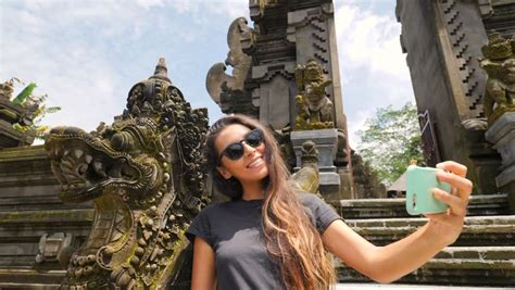Attractive Young Mixed Race Tourist Girl In Taking Selfie Photo With Mobile Phone At Balinese