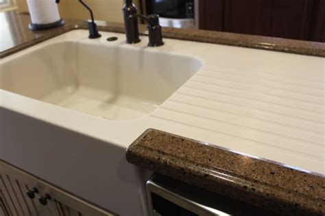 custom made corian farm sink with drainboard in a hanstone