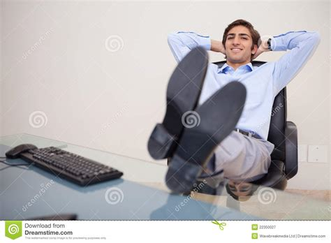 smiling businessman leaning back in his chair royalty free