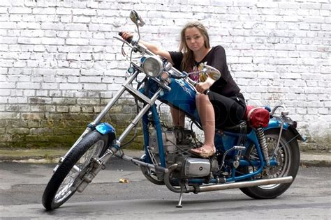 The Beautiful Woman Sits On A Motorcycle
