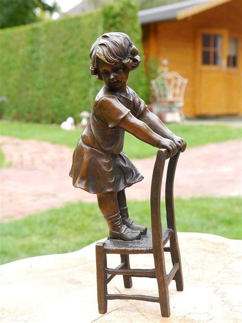 bronze figur eines kleinen maedchen auf einem stuhl