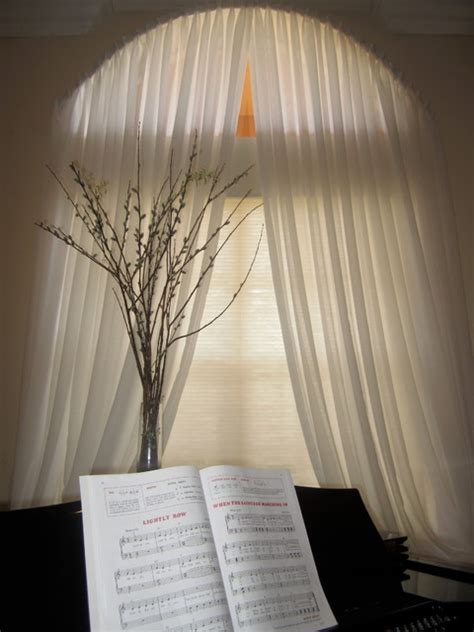 yardena arch window with pleated white sheer drapes