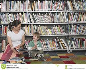 Woman Reading Book To Boy In Library Stock Photos - Image ...