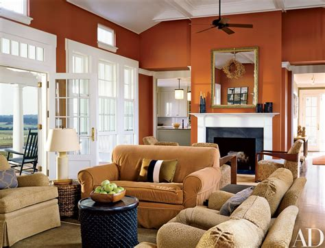 The slick orange wall and sofa stool stand out boldly in this living area. How to Decorate with Orange | Living room orange, Burnt ...