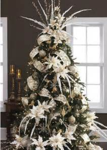 tree with white poinsettia and beautifully garland wire edge ribbon through this tree