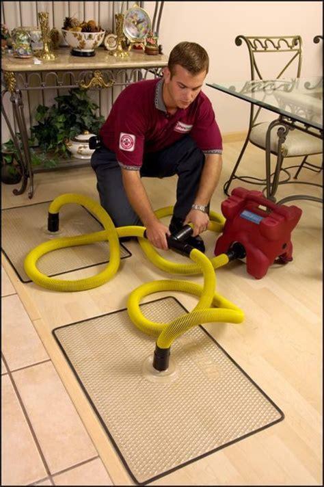 Hardwood Floor Drying Mats - water technician adding wood floor drying mats to save