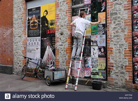 man pastes  posters   walls  clubs