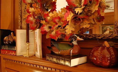 fall ornaments decorate a fireplace mantel for fall or autumn with books pumpkins and a fall wreath