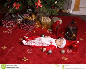 Cute Little Santa Baby Sleeping Beside Christmas Tree With ...