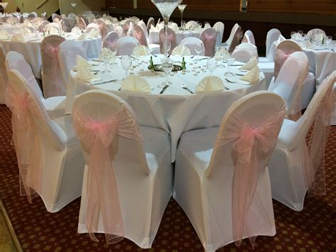 White Chair Covers With Pale Pink Organza Sashes At A