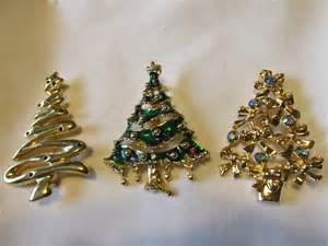 three vintage christmas tree pins with rhinestones enameling one marked avon pins
