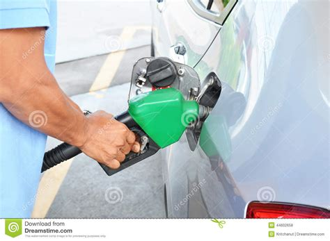 A Man Filling Up The Gas Tank Of A Car Stock Photo