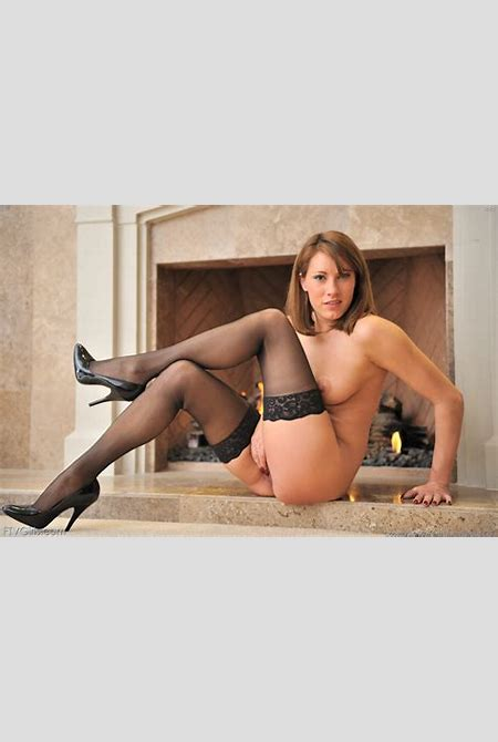 Big boobed Olivia Alize in black stockings shows her body by the fireplace and on the balcony