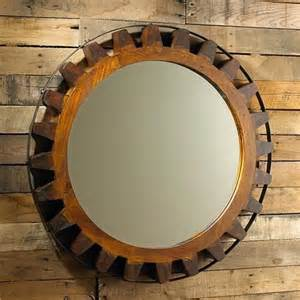 wooden gear mirror a solid wood carved gear is straped with a black iron for a rustic look