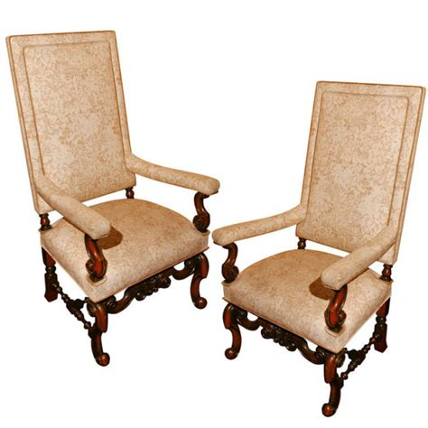 a pair of high back jacobean style walnut arm chairs for