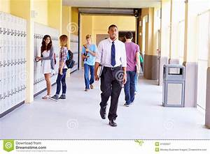 High School Students And Teacher Walking Along Hallway ...