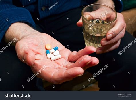 Close-up Old Man's Hands With Pills And Glass Of Water, He