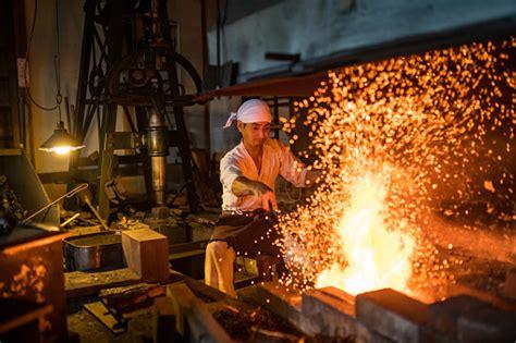 japanese blacksmith stokes  fire preparing  forge