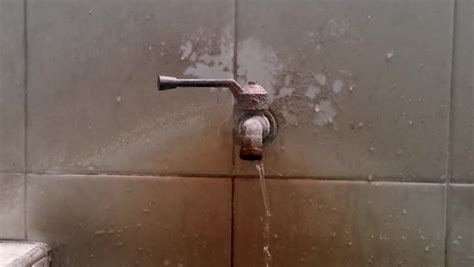 a macro of dripping bathroom faucet spout view from front