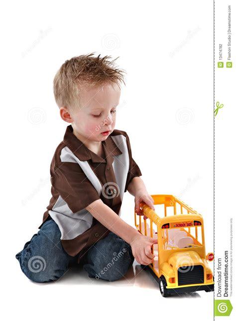 year  boy plying  yellow school bus toy stock