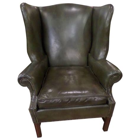 green leather chippendale style wing chair and ottoman at