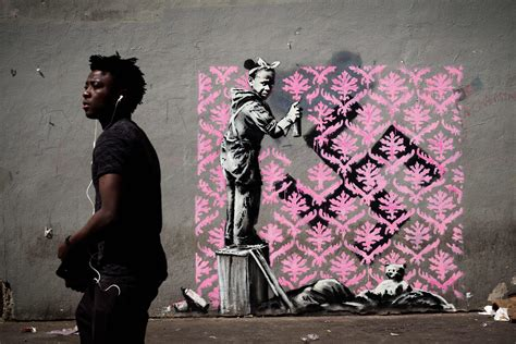 Street artist Banksy paints Paris with murals of migrants ...