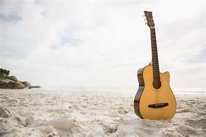 Acoustic guitar standing in the sand Photo | Free Download