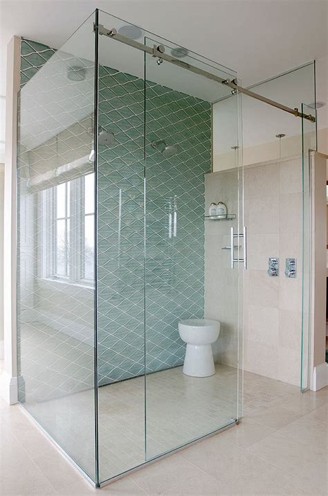 floor  ceiling glass shower  diagonal blue tile