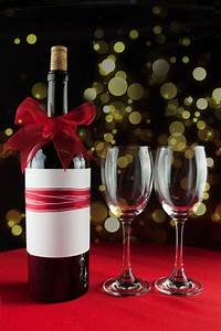 Wine bottle with a red ribbon and two empty glasses with ...