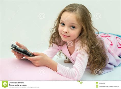 Happy Little Girl Lying On Bed With Tablet Computer Stock