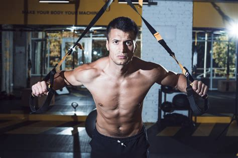 muscular man exercising  fitness strap  gym photo