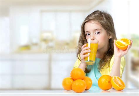 Child Girl Drinking Fresh Orange Juice Background. Stock